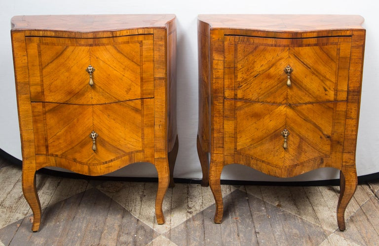 Pair of matching fruitwood (possibly olivewood) parquetry veneers. Each with 2 drawers. Shaped front, rococo legs. Each drawer is 7 inches deep. Drop pulls.