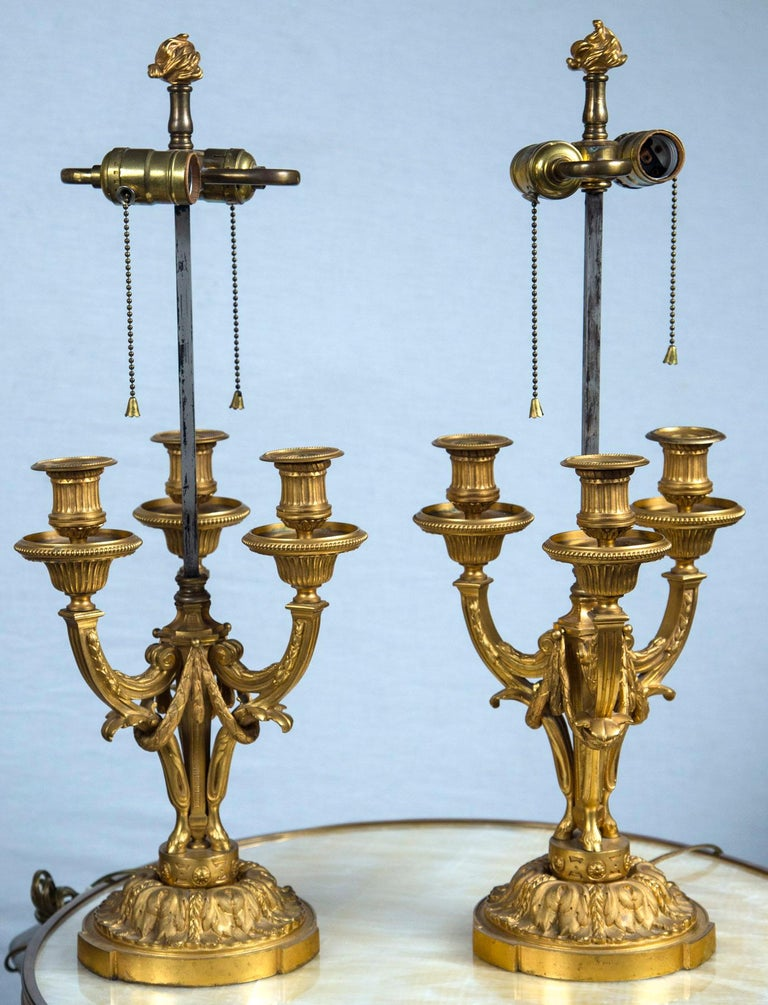 In the Louis XVI neoclassical style. Each with 3 candle arms. Decorated with acanthus leaves and swags. Very well chased and of great quality. Square steel rod supports light cluster. Gilt bronze flame finial.