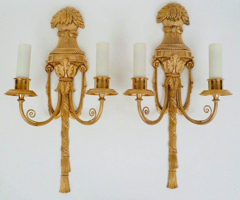 This handsome pair of gilt bronze sconces feature Classical motifs including acanthus leaves, swags and tassels. They are in excellent condition, retaining their original gilding, and are signed Caldwell.