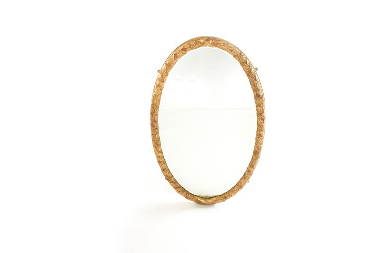 Beautiful pair of gilt wood framed beveled hanging wall mirror in an oval shape with heavily carved wreath branch details motif . The mirror is in good condition. Minor wear / loss to gilt wood frame. The gilt wood frames measure 59 inches high x 32