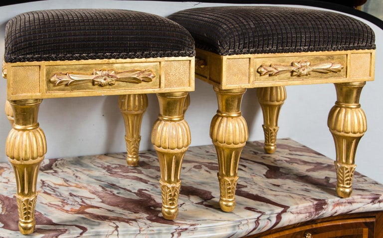 Carved in the English Regency style, gilded and upholstered in a deep brown fabric. Under side of the seat are labels from J Robert Scott.