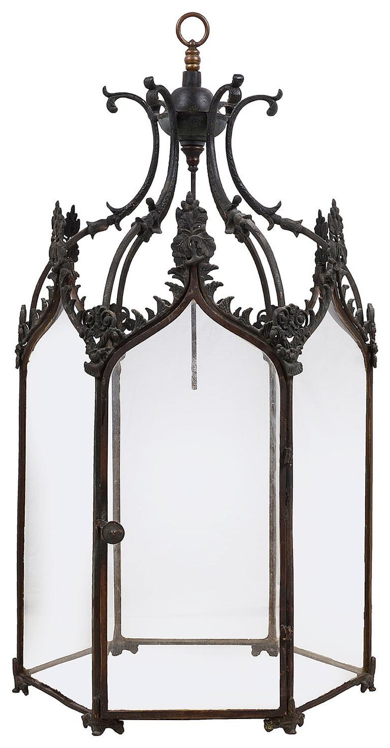 A good quality pair of 19th century bronze Gothic influenced hall lanterns, each with scrolling foliate and motif decoration, a hinged door and raised on scrolling feet.