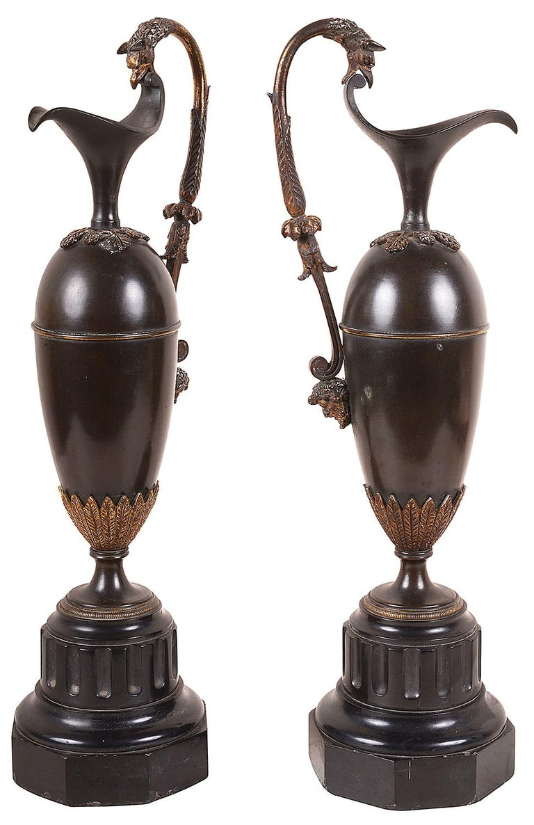 A good quality pair of neo-classical Grand Tour patinated bronze Ewers, each with scrolling gilded handles with Griffins and Bacchus influenced mask mounts, raised on black marble hexagonal fluted bases, circa 1820.