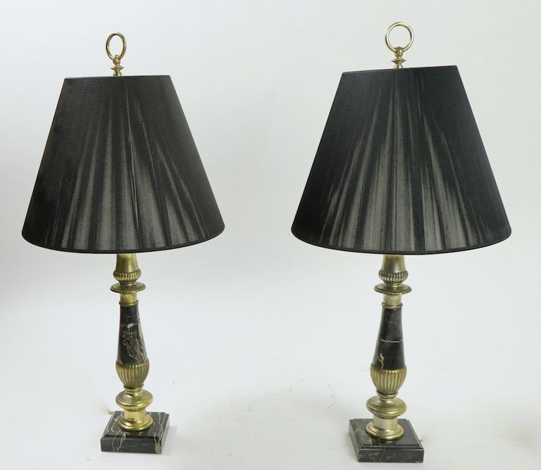 Stunning pair of polished black marble table lamps with decorative cast metal fitments. Both lamps are in very good, original and working condition, the metal elements show cosmetic wear to finish normal and consistent with age. Priced and offered