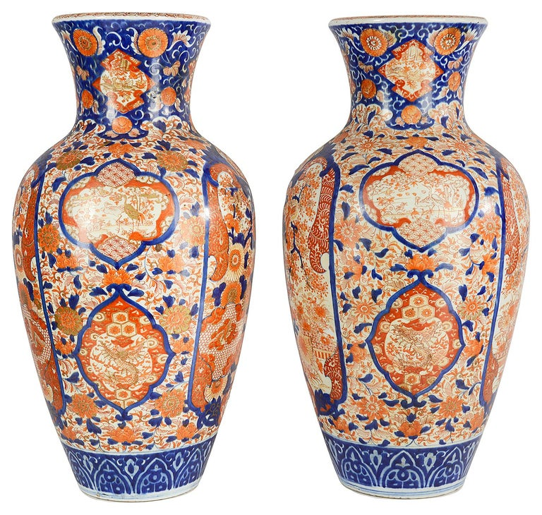 An impressive pair of late 19th century Japanese Imari vases, each with the classical orange and blue coloring. Exotic flowers, blossom and birds set in hand painted panels, motifs and symbols. This pair of vases can be converted to lamps within a