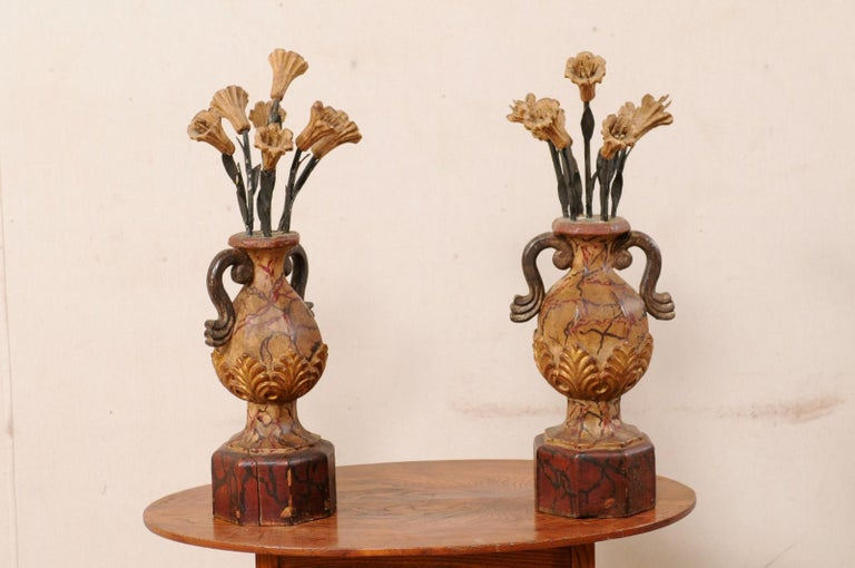 An Italian pair of carved wood urns from the early 20th century. This antique pair of decorations from Italy each feature a hand-carved, two-handled urn, which is raised upon a pedestal base, with a floral bouquet springing upward out from it's top.