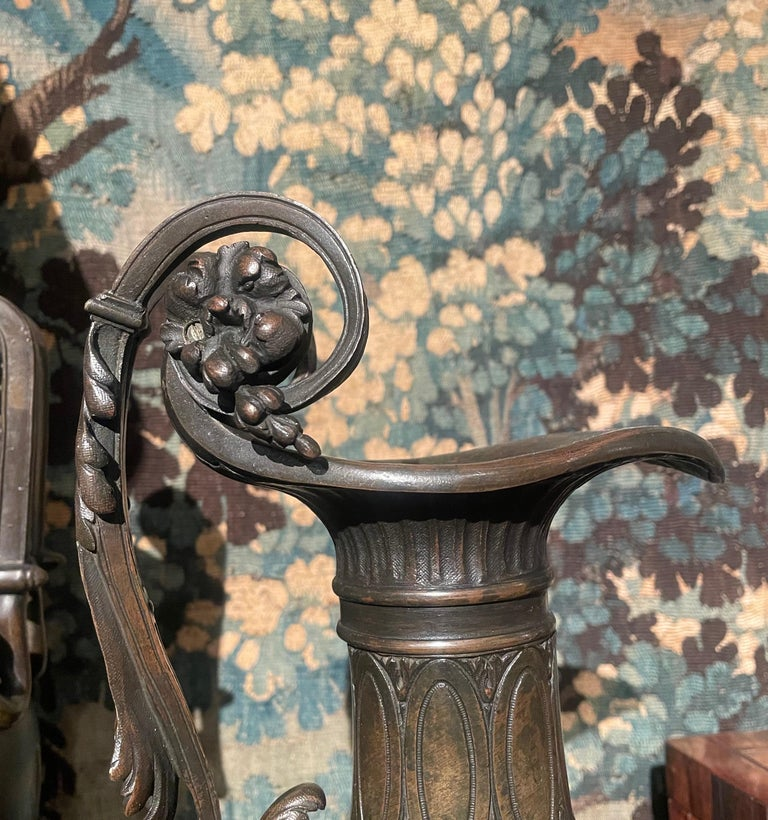 Pair of large Grand Tour ewers in bronze, circa 1870. These Italian ewers each with a curving wide-lipped mouth, and an ornately scrolling handle decorated with grapes and stylized foliage. With ribbing and oval cartouches to the neck, the body