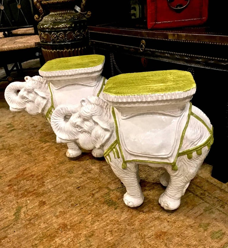 This is a great pair of c.1960s Italian ceramic garden stools or tables. These highly decorative white toned elephants are cast in fine detail and decorated with a lime green trimmed yellow seat. Both of the elephants are in overall excellent