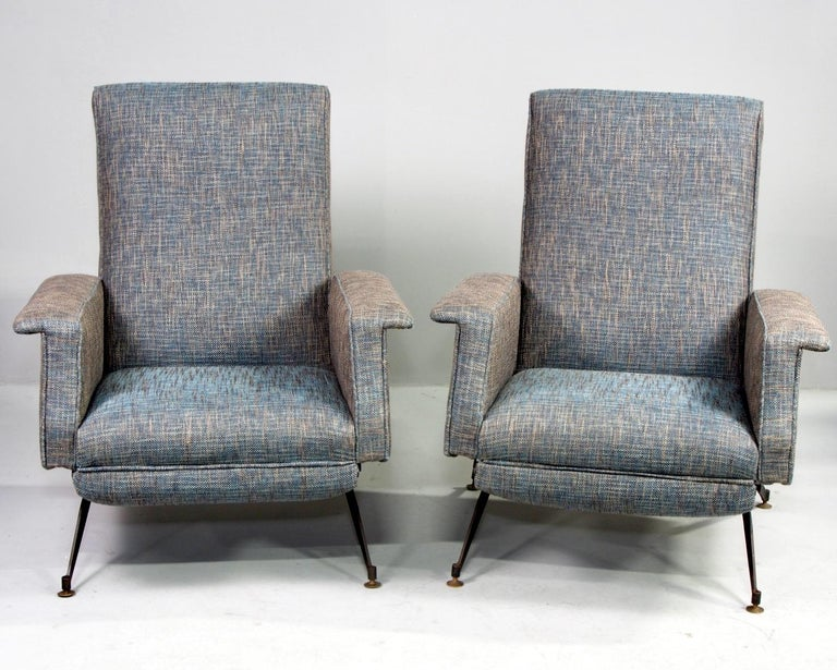 Italian pair of reclining armchairs have been professionally upholstered in blue and taupe tweed fabric, circa 1950s. Chairs feature slender black metal legs, flat-topped arm rests and tall seat backs that recline. These chairs have a manual