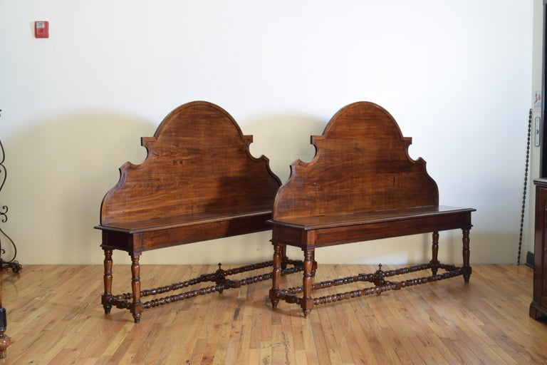 This well sized, as in manageable, pair of benches has Baroque shaped tall backrests above rectangular seats with molded edges, the underside of one of the seats with a secret storage area, raised on turned legs joined by turned box stretchers, the
