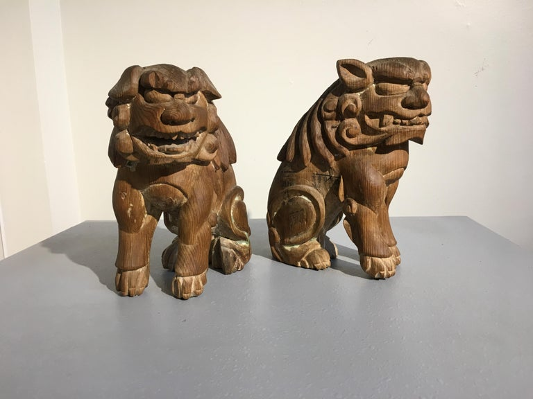 A charmingly grotesque pair of Japanese mingei (folk) carved guardian lions, komainu, Edo Period, early 19th century.   Each carved from a single block of hinoki (Japanese cypress) wood. They are portrayed seated on their haunches, hunched, as if