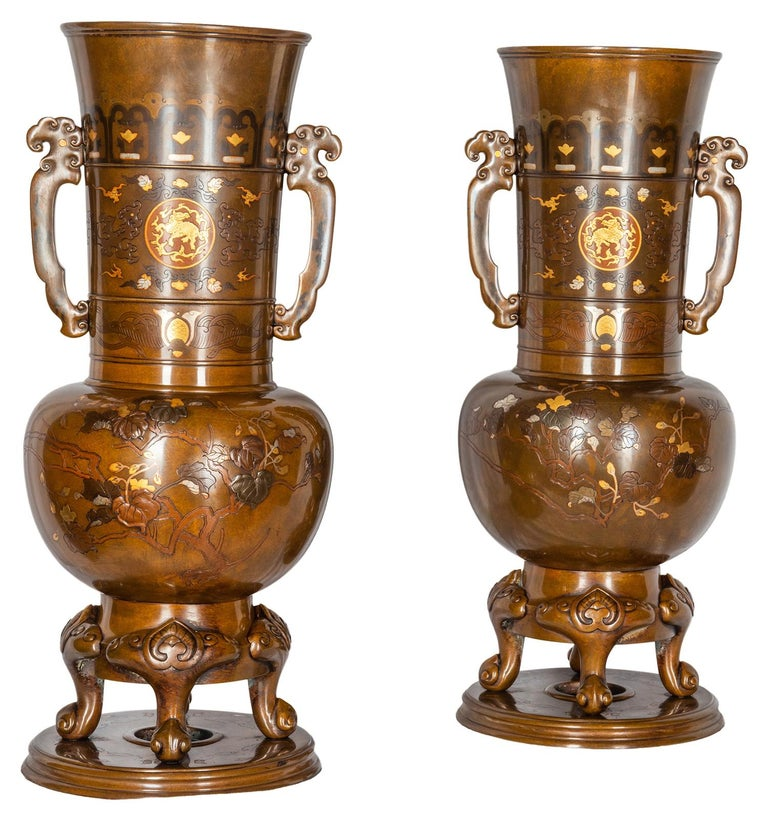 Pair of fine quality Japanese Meiji period (1868-1912) patinated bronze Miyao style gold and silver overlay two handled vases, each with twin handles, classical motif decoration with mythical creatures engraved and wonderful trees, leaves and buds.
