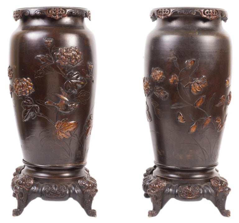 A good quality pair of Japanese bronze relief vases, each with chrysanthemum and leaf decoration in patinated and gilded bronze, birds flying and raised on bases with mythical masks.