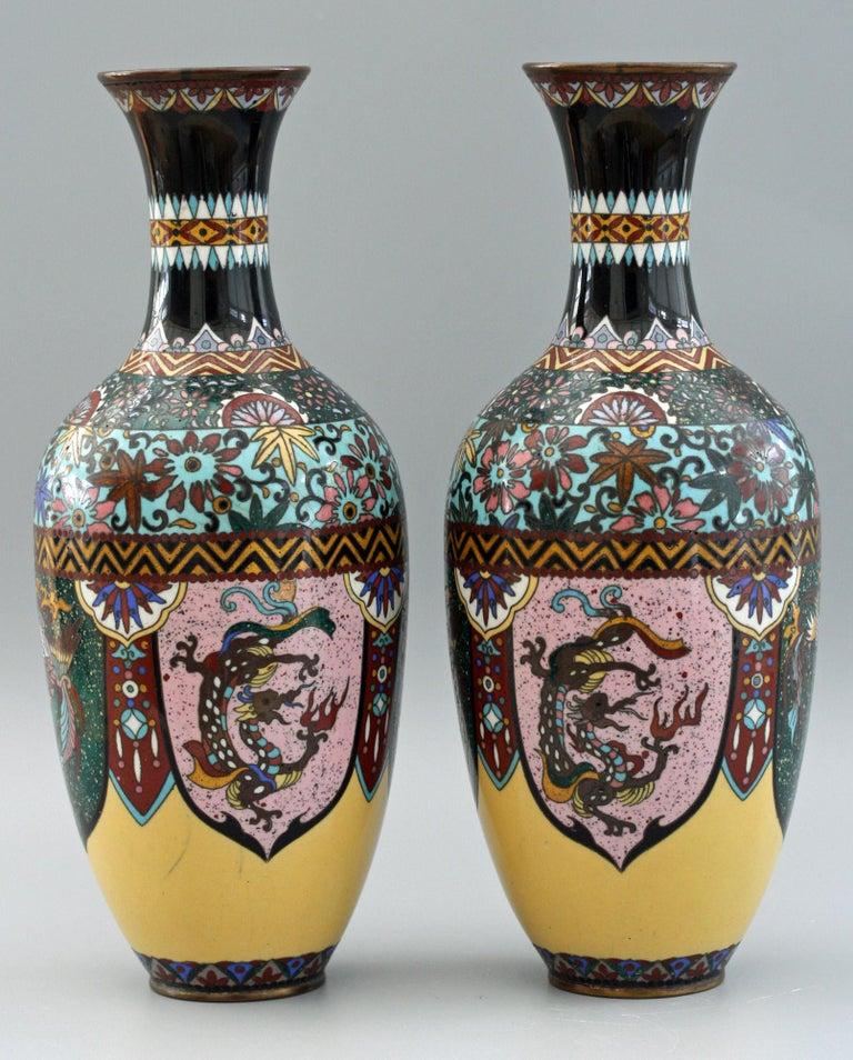 A very decorative pair antique Japanese Meiji period Rooster and Dragon panel cloisonné vases dating from the latter 19th or early 20th century. These striking vases stand on a narrow rounded foot with rounded baluster shaped bodies and narrow