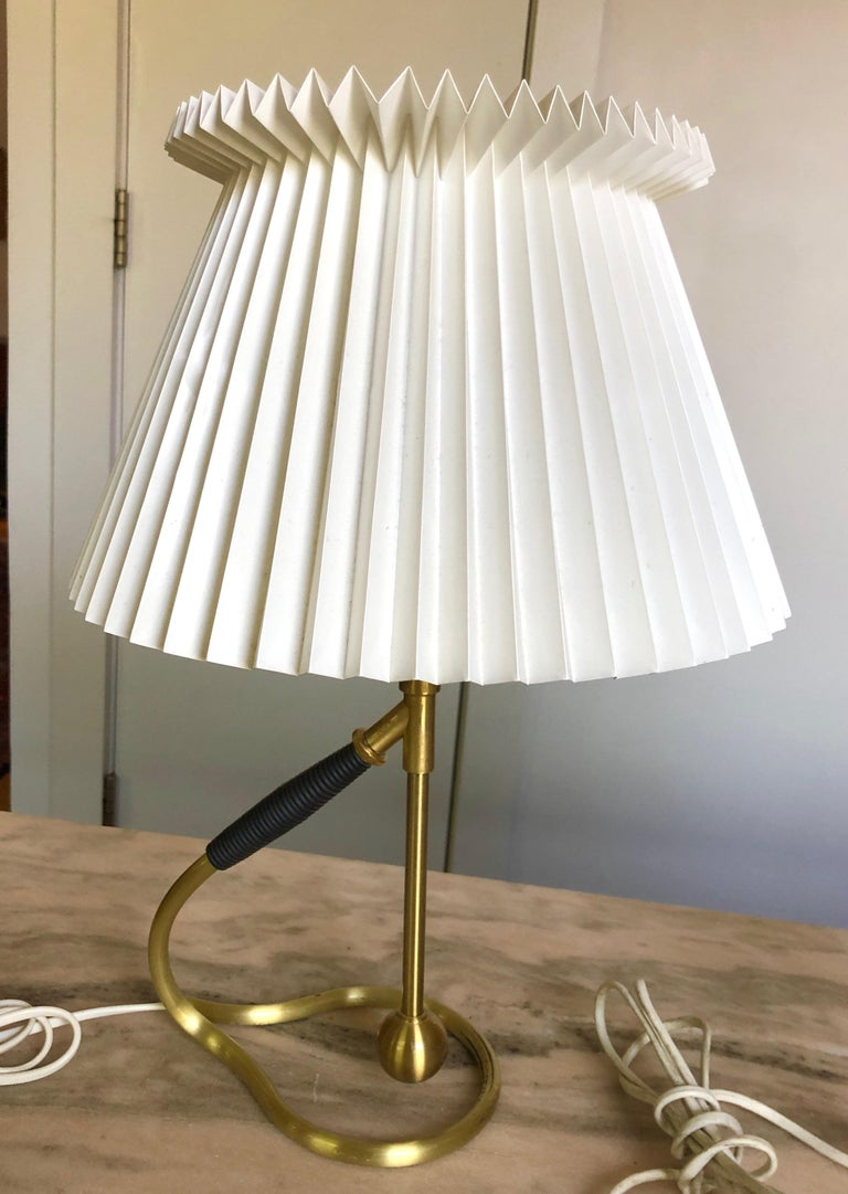 Brushed brass, faux leather wrapped handle, original pleated shade. Designed in the 1940s, this vintage pair is likely from the 1960s. The sculptural ingeniously transforms from table lamp to wall sconce by tilting the free-floating pendulum in the