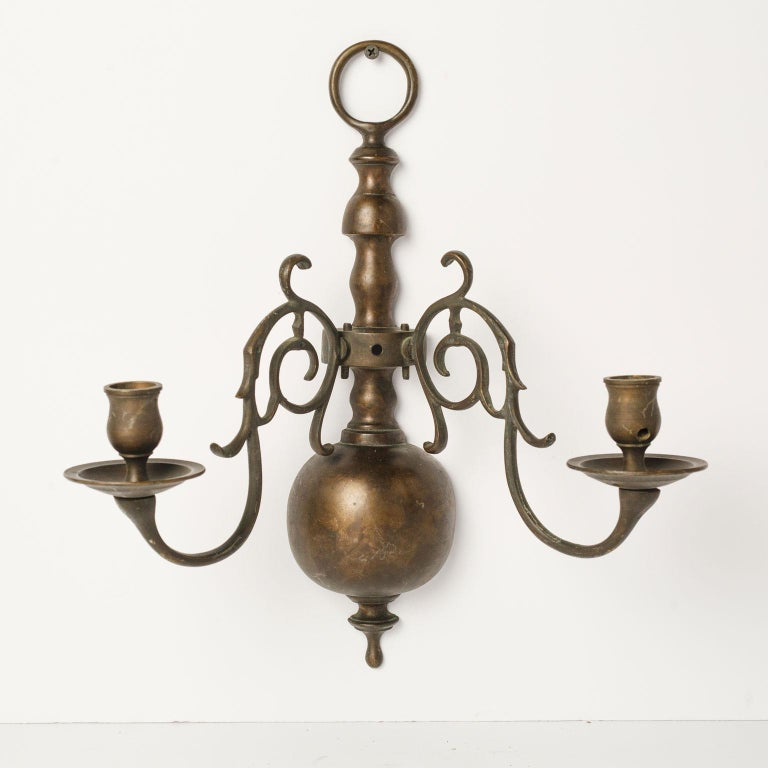 Pair of large bronze two-arm sconces in a nice, dark rich natural patina. Flemish or Dutch style and unwired. Can be wired for electricity for an additional cost. Sold together as a pair for $1,700.