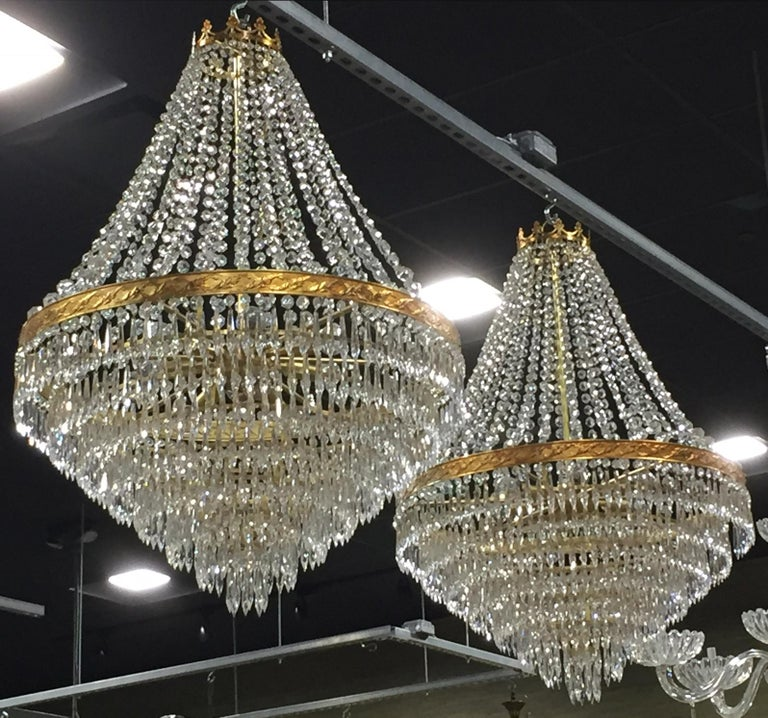 Pair of circa 1980s Italian wedding cake style chandeliers that each have eight tiers of crystal pendants and nine candelabra sockets. The decorative brass frames support draped crystal swags and chandeliers are topped with brass crown. New wiring