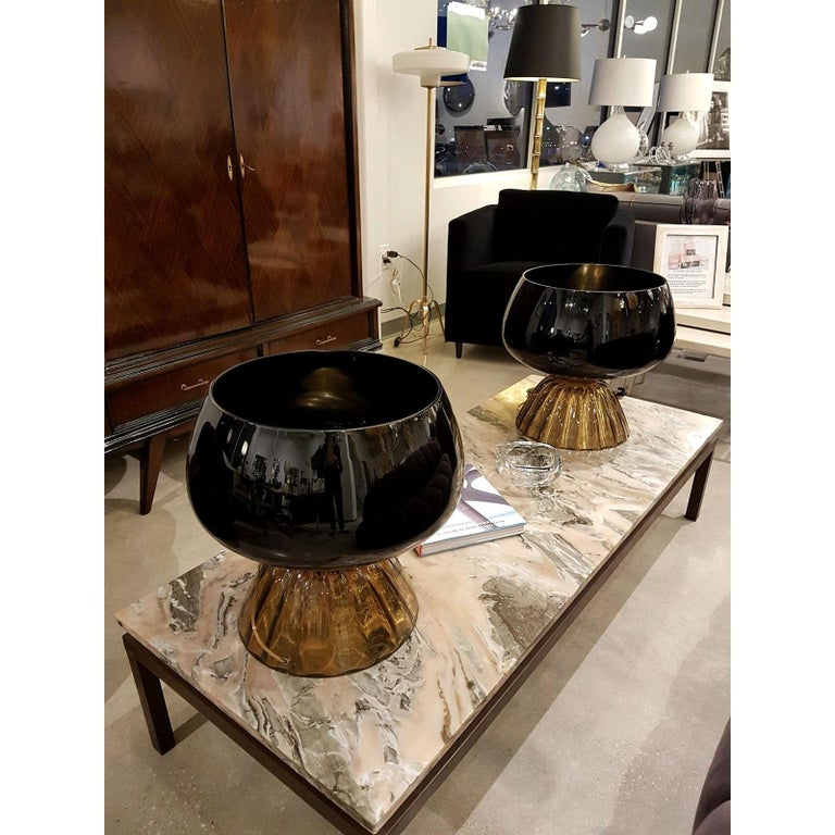 Pair of large Mid-Century Modern Murano glass table lamps with black almost opaque tops and brown transparent bases. Attributed to Cenedese, Italy, late 1960s Brass fittings. The light is coming up, out of the large black top vase, and shows a