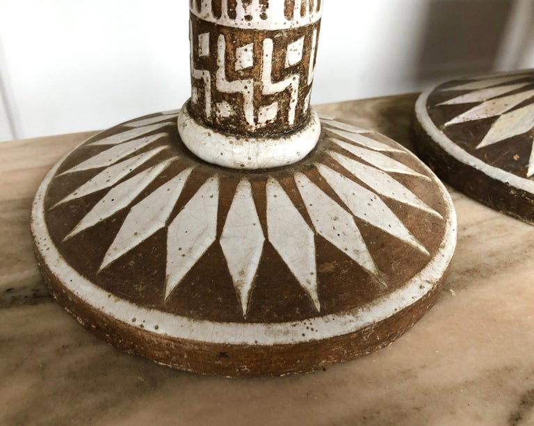 """Hand-decorated, white glaze on brown pottery, employing abstract geometric patterns, signed to underside with artist cipher and """"For B. Altman & Co."""", circa 1950s.  Ceramic base is 21"""