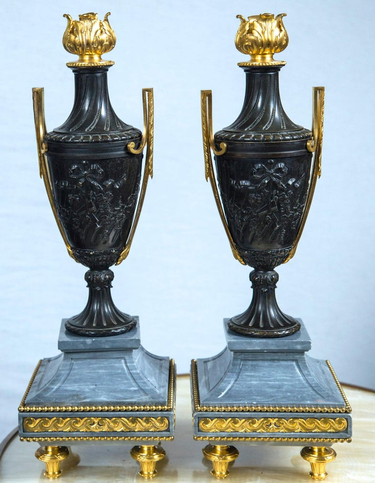 Raised on gilt bronze toupee feet. Gilt decoration on 3 sides of the grey marble bases Gilt bronze handles. Gilt bronze floral finial. The patinated bronze decorated in relief with bow topped trophies on each side. The bases measure 6.5 x 6.5. The