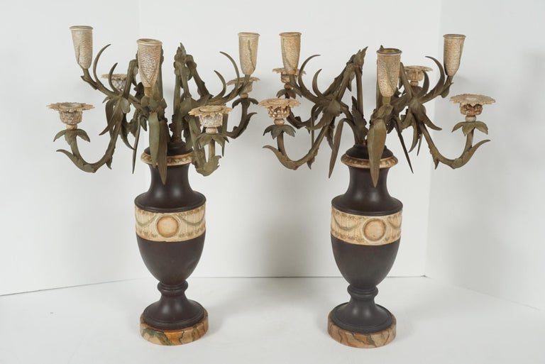 This pair of candelabra made in the form of urns holding floral arrangements are French and were cast in bronze in the 1870s. It's possible that at one time they were gilded but they now are tole painted and appear to have been so for some time. The