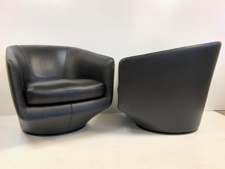 Pair of black leather swivel lounge chairs designed by Neils Bendsten. The chairs have a metal swivel base that rotates 360°.