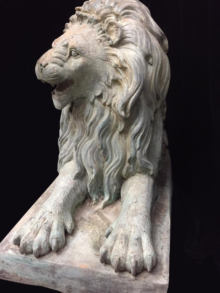 Outstanding pair of Continental opposing lifesize weathered green patinated bronze lions in a lying position on a solid bronze base. Meticulous attention given to every detail with beautiful face impressions. Second half of the 20th century.  One