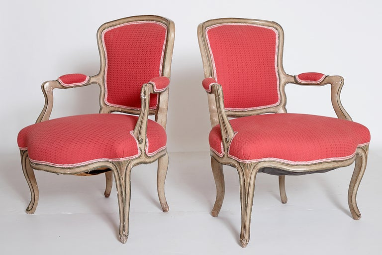 A pair of Louis XV fauteuils / open armchairs grayish-green painted frame, carved details picked out in a darker hue, textured woven coral / watermelon upholstery with lighter color trim, France, 18th century.  The chairs have slightly different