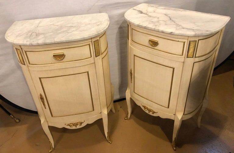 Pair of Louis XV style painted and bronze mounted demilune nightstands or end tables each having a conforming removable white and gray veined marble top. The pair having one drawer above a large door having a fitted shelf. The pair with bronze