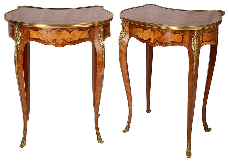 A good quality pair of Louis XVI style parquetry inlaid ormolu-mounted side tables, each with a single frieze drawers and raised on elegant cabriole legs terminating in scrolling ormolu feet.
