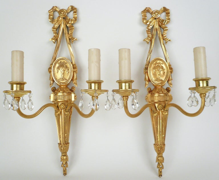 This pair of gilt bronze sconces feature Neo-Classical motifs including bowknots, acanthus leaves, and oval medallions featuring baskets of roses. They retain their original finish, and are signed Caldwell.