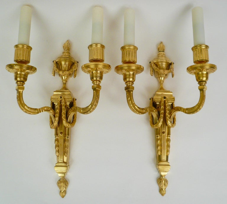 This finely details pair of Louis XVI style sconces feature Neo-Classical motifs including urns. swags and acanthus leaves. They retain their original gilding and are signed Caldwell.