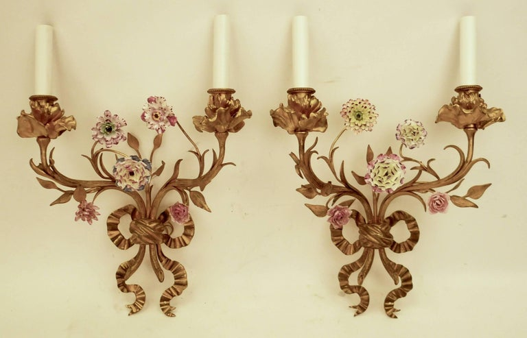 This fine pair of cast bronze foliate, and bow knot motif sconces feature hand-painted porcelain flowers.