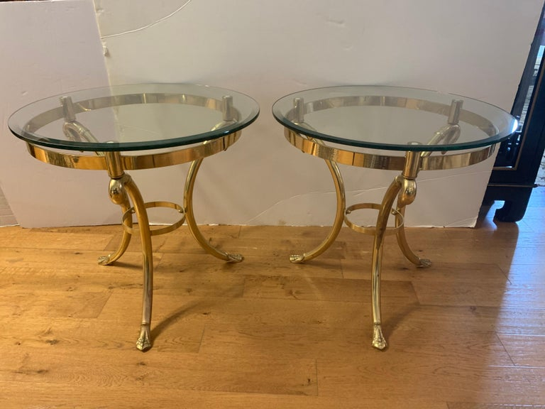 Two elegant Maison Jansen mid-century neoclassical end tables, gueridons or nightstands with beveled glass tops and three legged brass base with swan heads and feet.