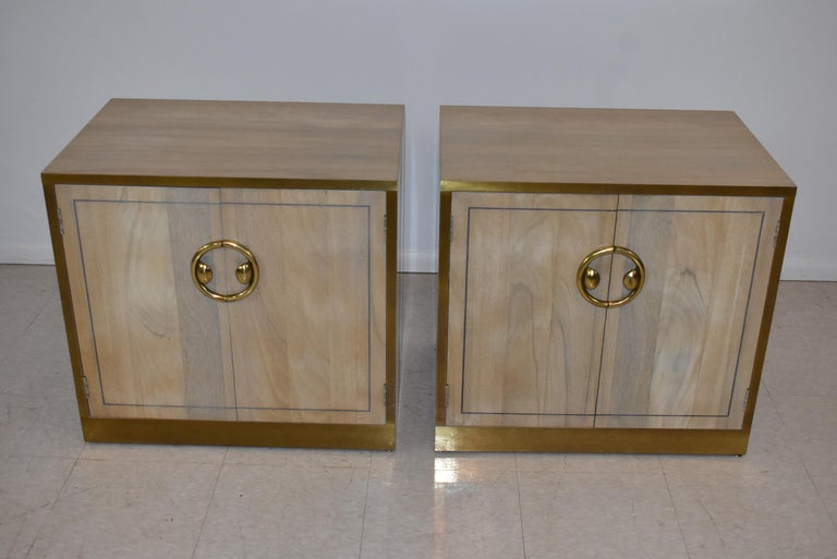 Pair of Zebrano wood and brass nightstands. Banded brass edges with circular brass pull on upper drawer. One adjustable shelf.