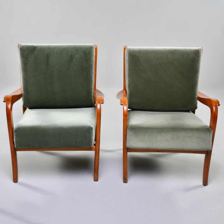 """Pair of circa 1950s Italian armchairs feature curvy cherry frames with slatted backs and loose, removable cushions newly upholstered in sage green velvet. Unknown maker. Sold and priced as a pair.   Measures: Arm height: 20"""" to 22.5"""" seat height:"""