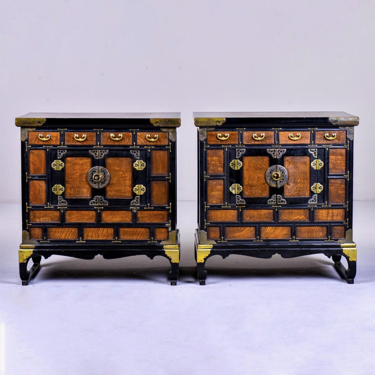 Pair of Korean side cabinets with grained wood and contrasting ebony stained panels with brass trim and hardware, circa 1950s. Curved feet with attached front-to-back rail, brass trimmed legs, decorative open work cabinet hinges and hardware, open