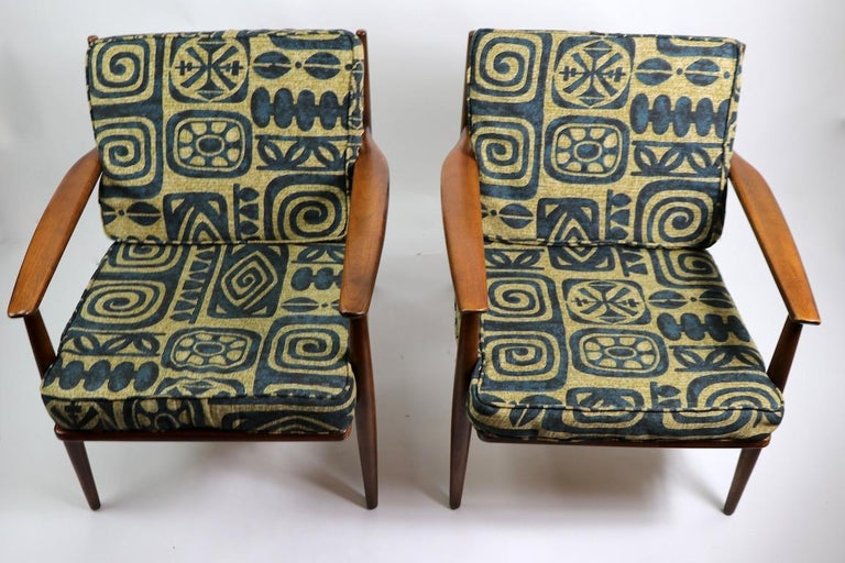 Pair of open arm lounge chairs by Baumritter, with solid beech and ash frames, and original cushions, cushions show wear. Both are in very good original condition, we have replaced the straps which support the seat cushions. Frames are nice and