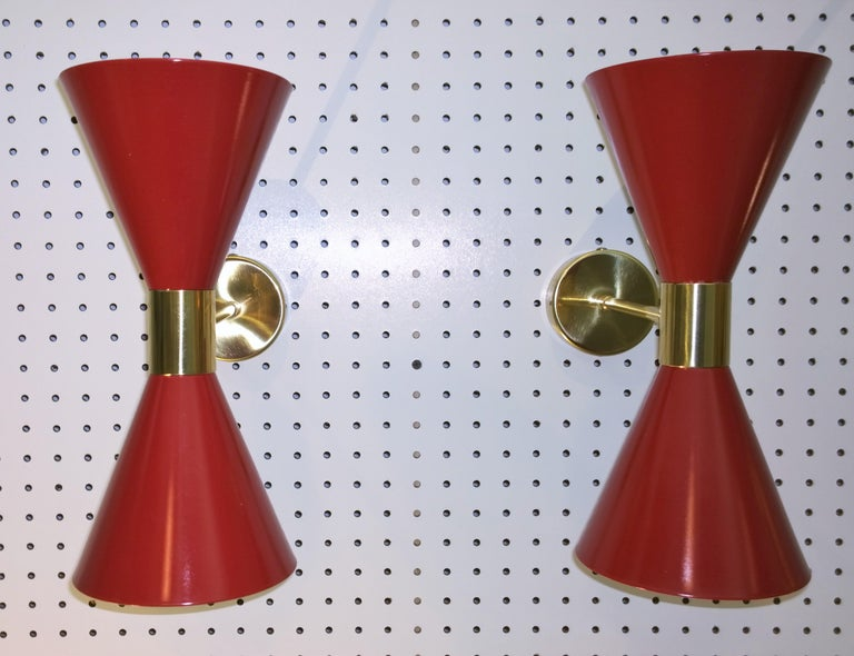 Offered is a pair of Mid-Century Modern Italian Stilnovo red exterior and white interior enameled aluminum double cone with brass accented hardware sconces. These Italian enameled sconces were produced in the 1950s-1960s and are vintage and not new