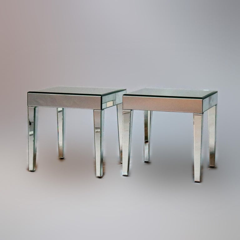 A pair of Mid-Century Modern side tables offer mirrored construction raised on tapered straight legs, circa 1960