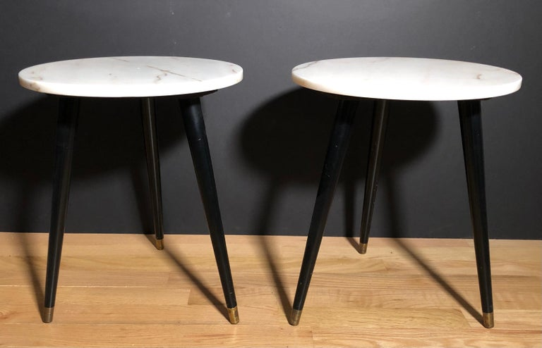 Pair of tripod Mid-Century Modern three leg round marble-top side tables. Off-white marble tops having a slight peach tone with a small amount of veining. Black painted legs with brass caps.