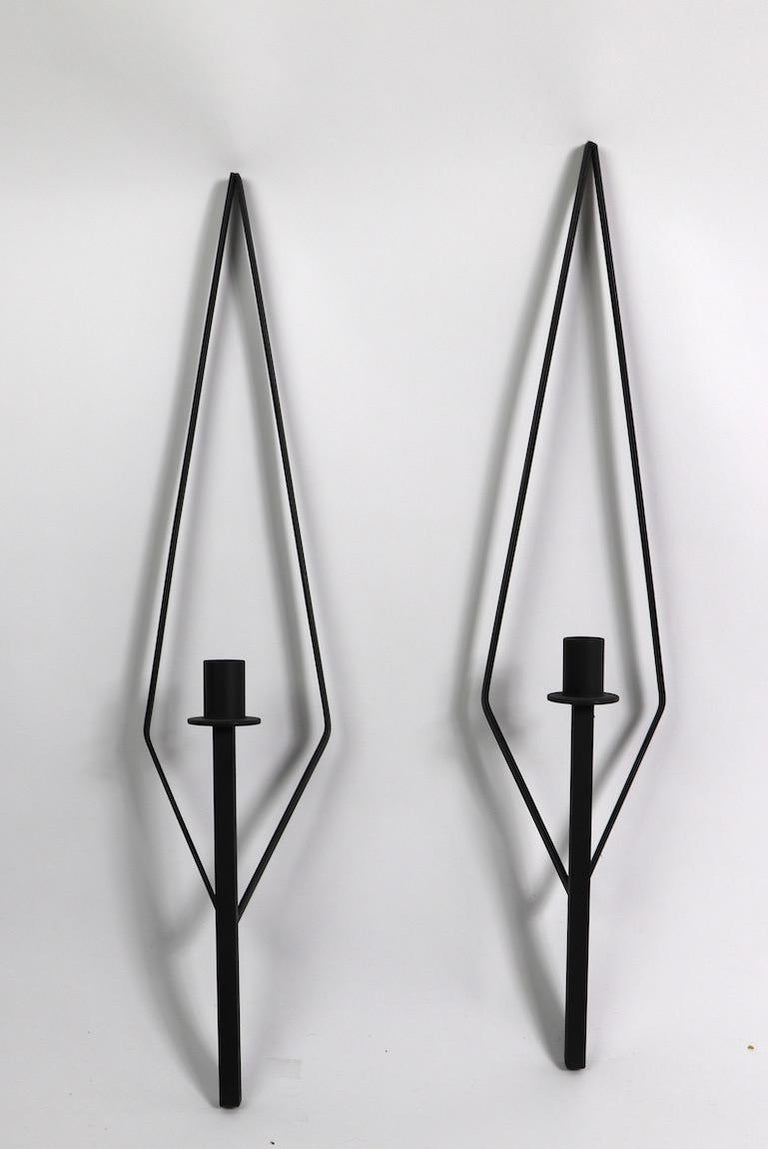 Elegant elongated diamond shaped backs support a single arm candle sconce. Wrought iron construction, clean, original condition. Matched pair selling together, design in the manner of Paul McCobb.