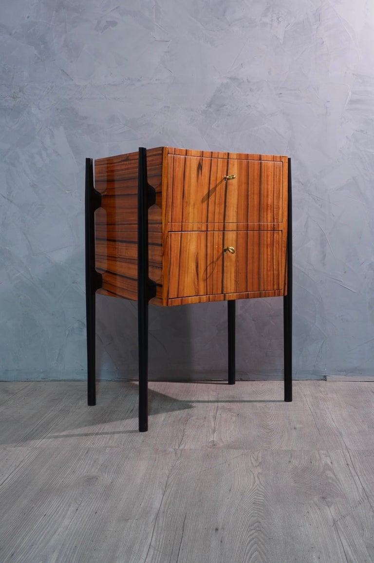 Pair of beautiful bedside tables with a very particular asymmetrical design, made even more eccentric by a very veined cherry wood.  The bedside tables have an asymmetrical wooden body, veneered in cherry wood. They have two drawers, which can be