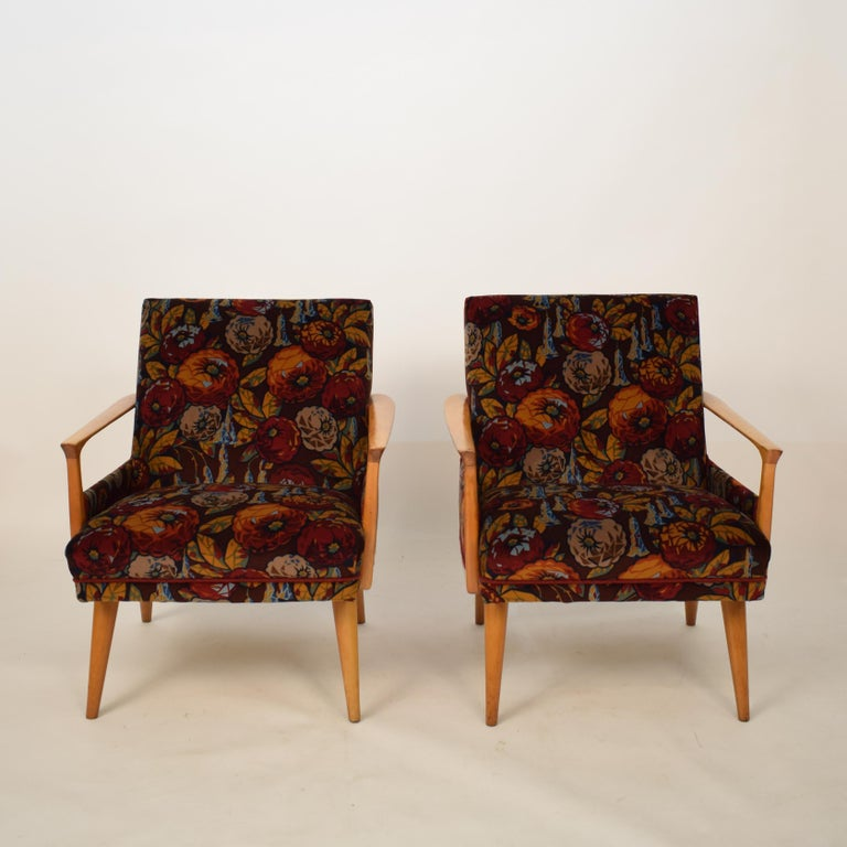 This elegant pair of midcentury armchairs were made in the 1950s in Italy. The are made out of beech and new upholstered in a multicolored flower velvet. The fabric is designed by Helge Stüssel and produced by Ratti in Italy. They are very