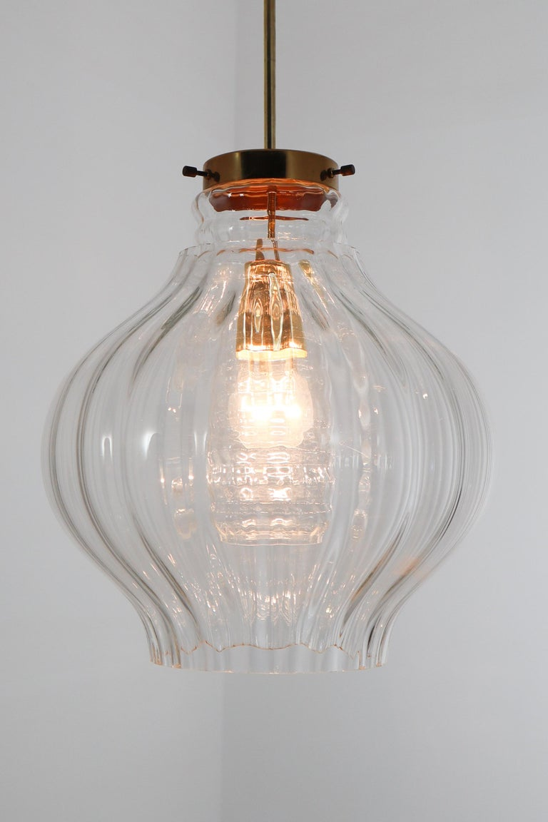 Wonderful pair of pendants, in glass and brass frame, Europe, 1960s the brass fixture beautifully combines with the clear glass. Due their materials and size, these lights will create a beautiful light-partition. Perfect original condition with a