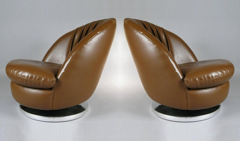 This pair of modern brown chairs designed by Milo Baughman for Thayer Coggin. These chairs are reminiscent of open scallop shells, the seats are deep and comfortable. Chairs rotate 360 degrees, tilt back and are mounted on chrome bases. Their