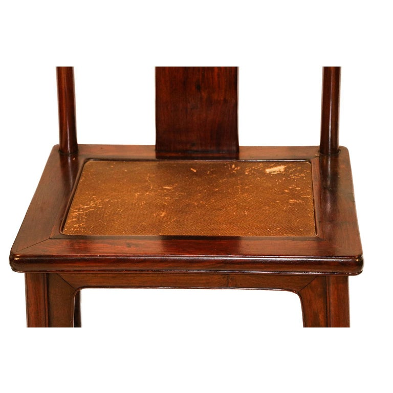An extraordinary pair of Chinese hardwood chairs crafted in the Ming Dynasty style, late 19th century. Each with inset rectangular panel hard cane seats supporting a wide slightly bowed rectangular back splat flanked by two upright circular posts