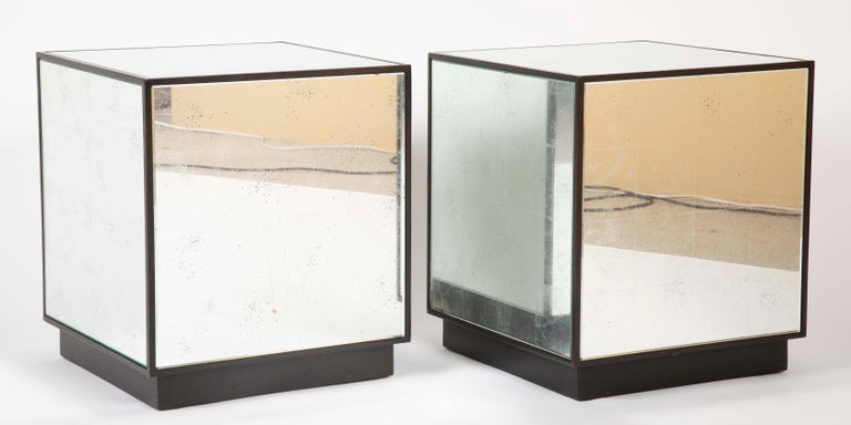 A pair of cube form side tables with mirrored surface on the top and all sides. Each panel of beveled antiqued mirror glass framed in dark wood set on a wood plinth. A very clean and modern look for bedroom, recreation or living room.