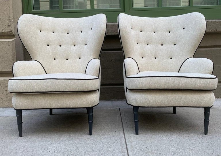 Pair of modern tufted wingback chairs. The chairs have a tufted back, painted wood legs with the front legs having a faux bamboo pattern.