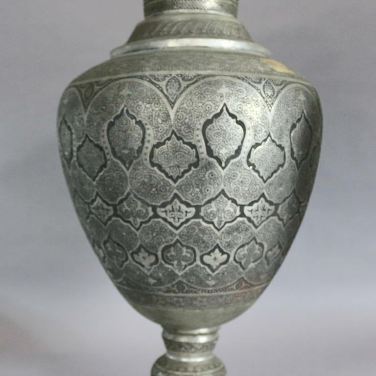 A pair of monumental Persian floor urns offer hand-hammered repeating Islamic patterns including paisley and arched geometric and arabesque designs, bulbous vessel is raised on stepped base and has neck terminating in flared mouth, 19th